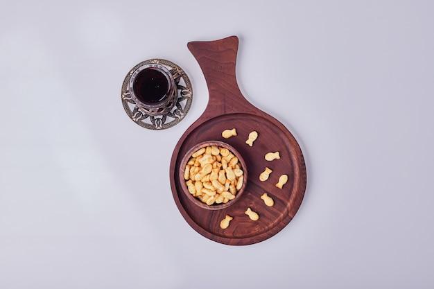 Biscoitos salgados em uma xícara de madeira com um copo de chá, vista de cima.