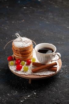 Biscoitos sanduíche de frente com recheio de creme junto com canela e café na superfície escura.
