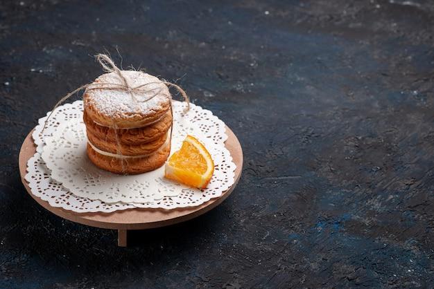 Biscoitos sanduíche deliciosos amarrados de frente com uma fatia de laranja no bolo de mesa azul escuro