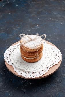Biscoitos sanduíche deliciosos de frente amarrados gostosos no bolo de mesa azul escuro