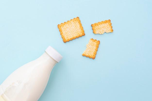 Biscoitos secos quebrados e garrafa de leite sobre fundo azul, vista superior, esquematizar. foto do conceito sobre comida e café da manhã