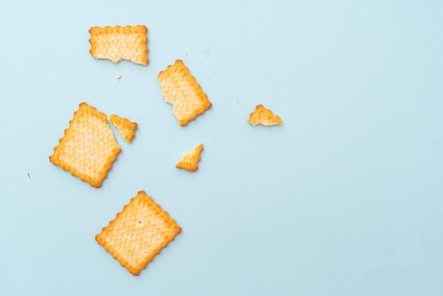 Biscoitos secos quebrados no fundo azul, vista de cima, disposição