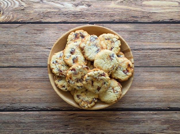 Biscoitos suculentos frescos da data em uma bacia em uma superfície de madeira marrom.