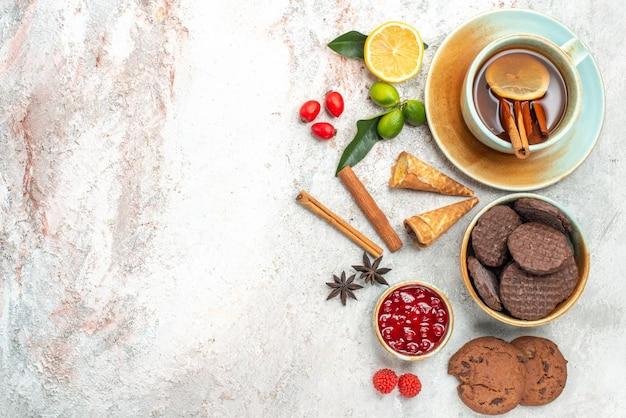 Biscoitos tigela de geléia biscoitos de chocolate uma xícara de chá com limão e canela em pau