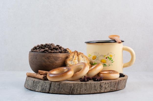 Biscoitos, tigela de grãos de café e xícara na peça de madeira