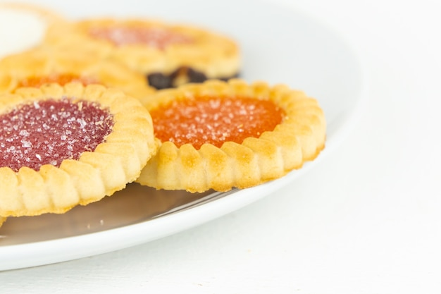 Biscoitos tortinhos com recheio de geleia de frutas em um prato branco