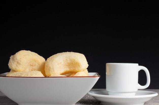 Biscoitos tradicionais de queijo brasileiro em uma tigela, uma xícara de café.