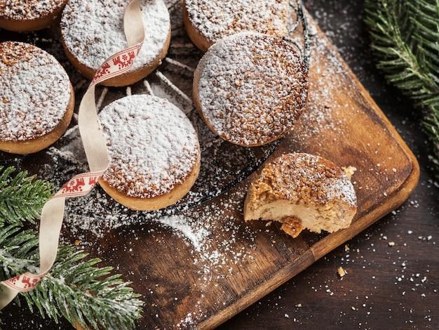 Biscoitos tradicionais do natal com amêndoas e sésamo no fundo de madeira escuro com espaço da cópia.
