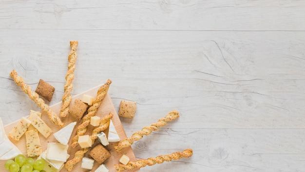 Biscoitos, varas de pão, queijo bloco e uvas no canto da superfície de madeira