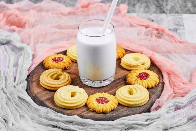 Biscoitos variados e um pote de leite em um prato de madeira com toalhas de mesa