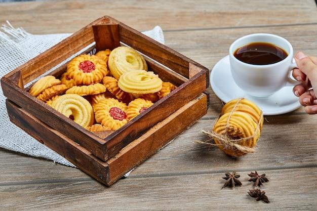Biscoitos variados e uma xícara de café na mesa de madeira.