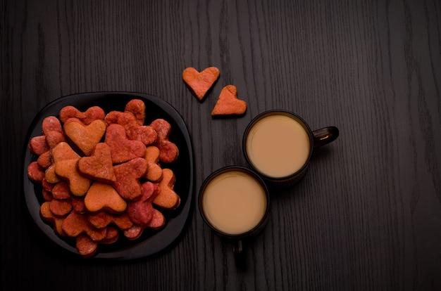 Biscoitos vermelhos em forma de coração e duas canecas de café com leite em uma mesa preta. dia dos namorados