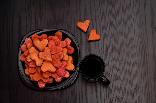 Biscoitos vermelhos em forma de coração em um prato preto, caneca de café, dia dos namorados