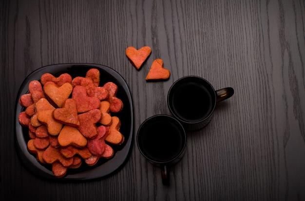 Biscoitos vermelhos em forma de coração em um prato preto, duas canecas de café, vista superior