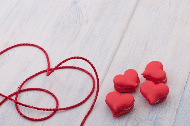 Biscoitos vermelhos em forma de coração em uma placa de madeira e decorados com fita no dia dos namorados