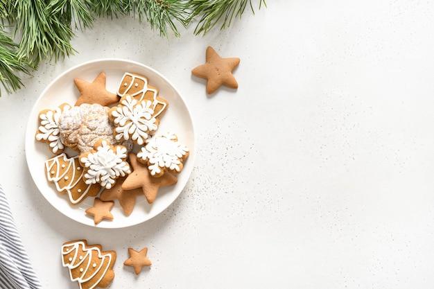 Biscoitos vitrificados artesanais de natal no prato decorado ramos de abeto no fundo branco. vista de cima. postura plana.