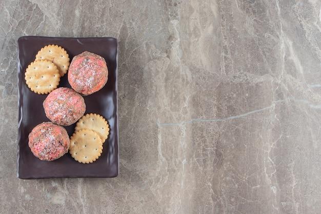 Biscoitos vitrificados e bolachas em uma travessa em mármore.