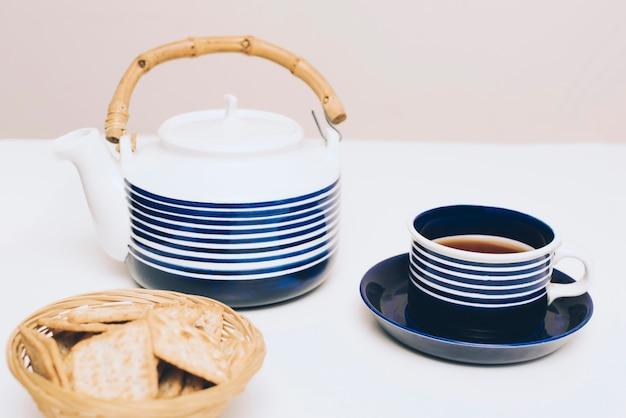 Biscoitos; xícara de chá e bule na mesa branca