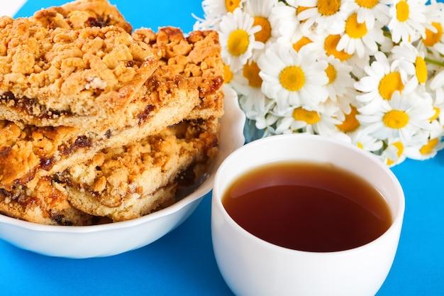 Biscoitos, xícara de chá e um buquê