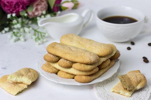 Biscuit cookies savoyardi, café e flores em uma superfície de mármore branco