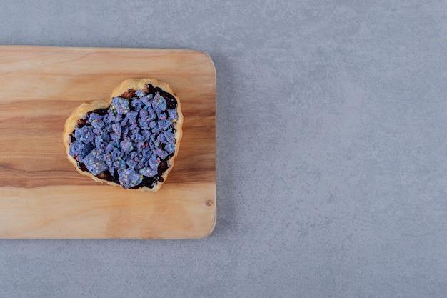 Biscuti em forma de coração na placa de madeira