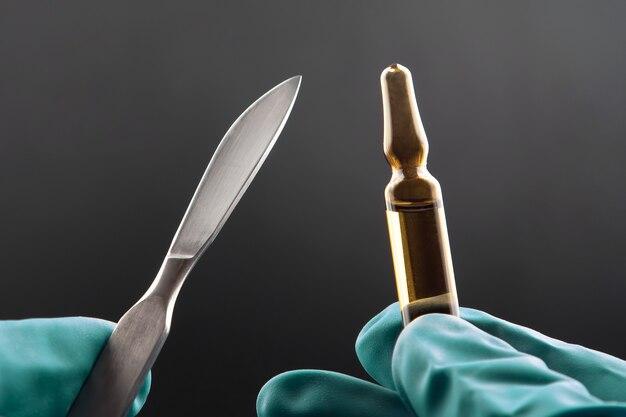 Bisturi médico e frasco para injeção nas mãos usando luvas. farmacologia, medicina e tratamento de doenças