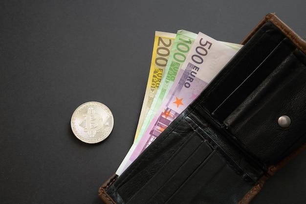 Bitcoin ao lado de notas de euro saindo de uma carteira em fundo preto. moeda digital, mercado de cadeia de blocos. notas de euro ao lado da moeda criptográfica