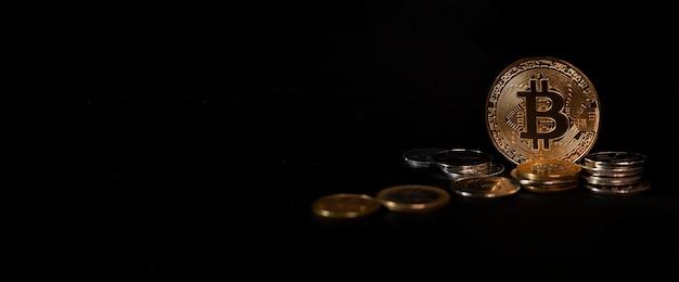 Bitcoin brilhante parado entre moedas em fundo preto