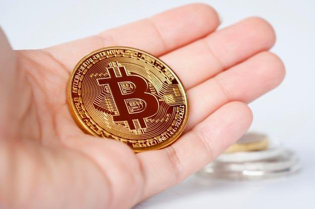 Bitcoin closeup na mão da mulher em fundo desfocado brilhante