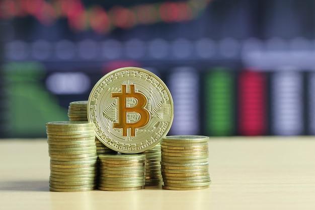 Bitcoin colocado na moeda de ouro da pilha no assoalho de madeira.