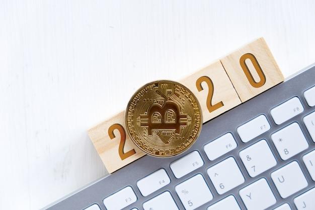 Bitcoin com números 2020 em cubos de madeira em um teclado branco