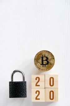 Bitcoin com números 2020 em cubos em um fundo de madeira branco uma fechadura.