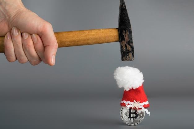 Bitcoin com um chapéu de papai noel e um velho martelo sobre uma superfície cinza. fechar-se