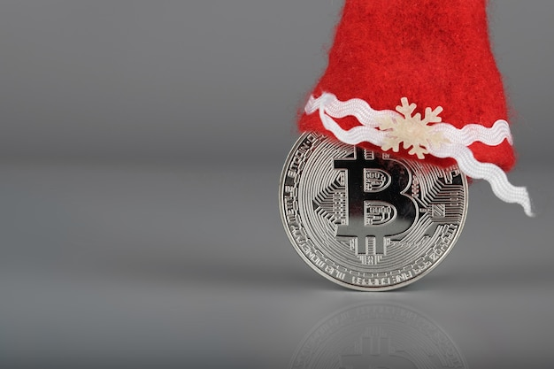 Bitcoin com um chapéu de papai noel em uma superfície cinza. fechar-se