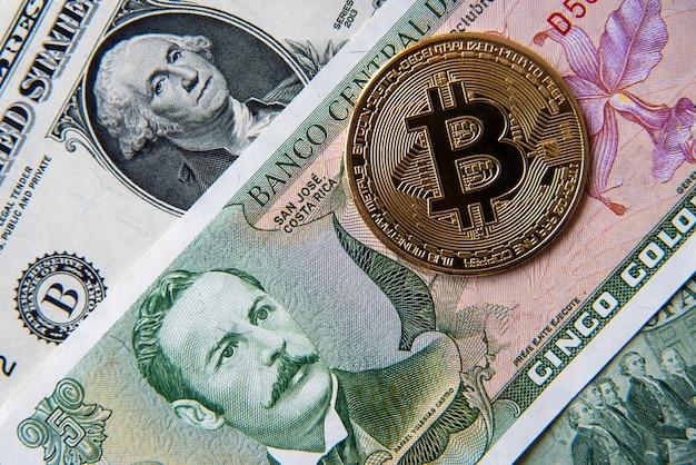 Bitcoin contra colones da costa rica e dólar americano, imagem de close-up. imagem conceitual de criptomoeda digital em comparação às moedas tradicionais do mundo