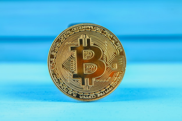 Bitcoin crypto da moeda da moeda de ouro em uma tabela azul.