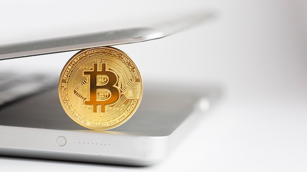 Bitcoin de close-up com laptop desfocado