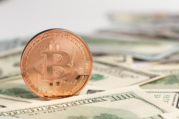 Bitcoin de cobre em cima de notas de dólar