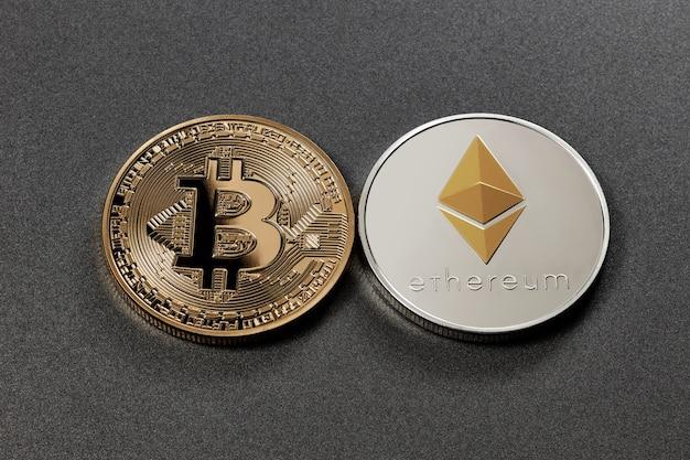 Bitcoin de moeda de ouro e ethereum de moeda de prata em uma superfície escura. conceito de negociação de criptomoeda e blockchain
