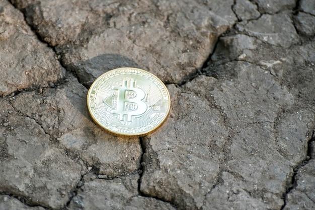 Bitcoin de moeda em solo rachado. conceito financeiro