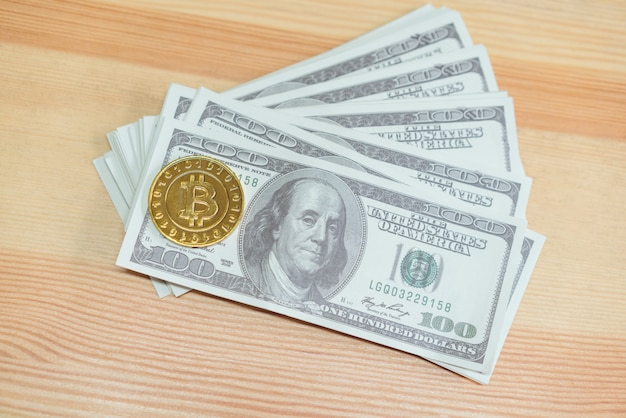 Bitcoin de ouro colocado em notas de 100 dólares