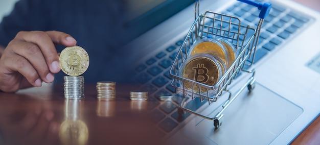 Bitcoin de ouro no carrinho de compras no computador portátil, troca de dinheiro em moeda digital com criptomoeda, block chain e conceito de finanças.