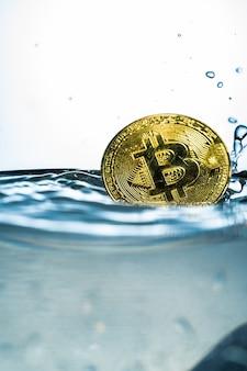 Bitcoin do ouro com respingo da água no fundo branco.