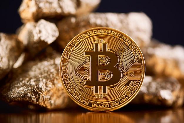 Bitcoin dourado brilhante que é o maior cryptocurrency no mundo inteiro na frente das protuberâncias do ouro no fundo preto.