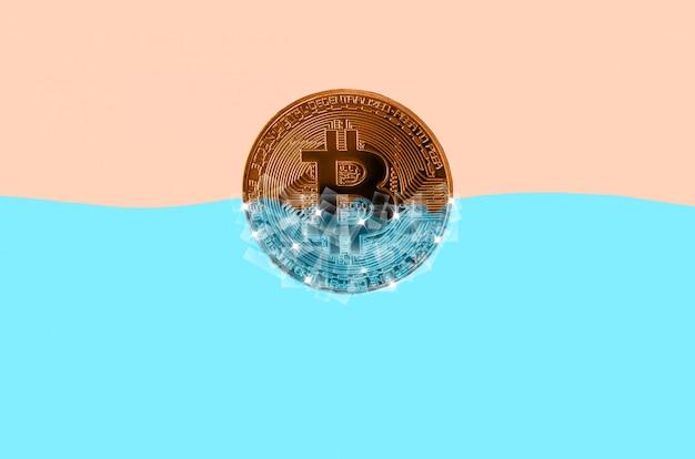 Bitcoin dourado congelado em blocos de gelo na água azul