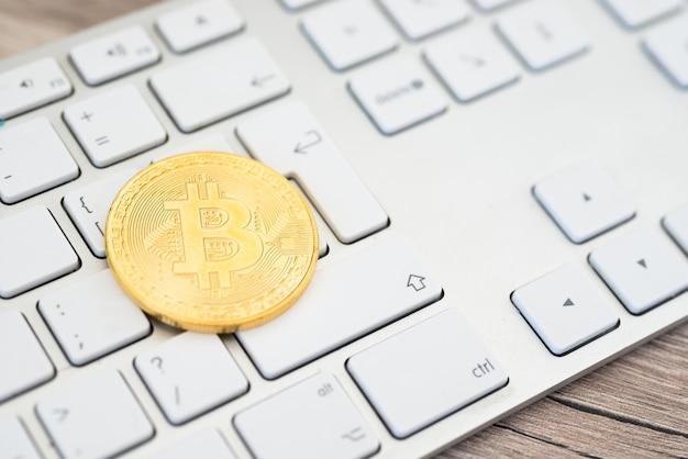 Bitcoin dourado deitado em um teclado branco