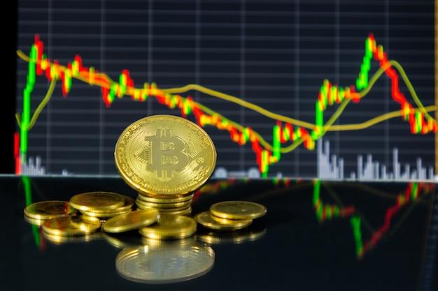 Bitcoin dourado e gráfico de ações em comprimidos.