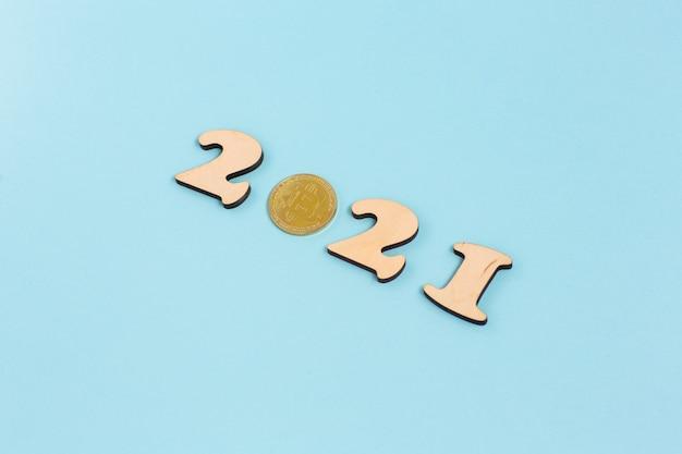 Bitcoin dourado e números de madeira 2021 sobre uma superfície azul