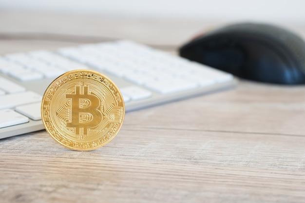 Bitcoin dourado em uma mesa de madeira perto de teclado branco e mouse de computador. conceito de mineração de dinheiro eletrônico