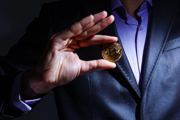 Bitcoin dourado na mão de um homem, símbolo de digitall de uma nova moeda virtual